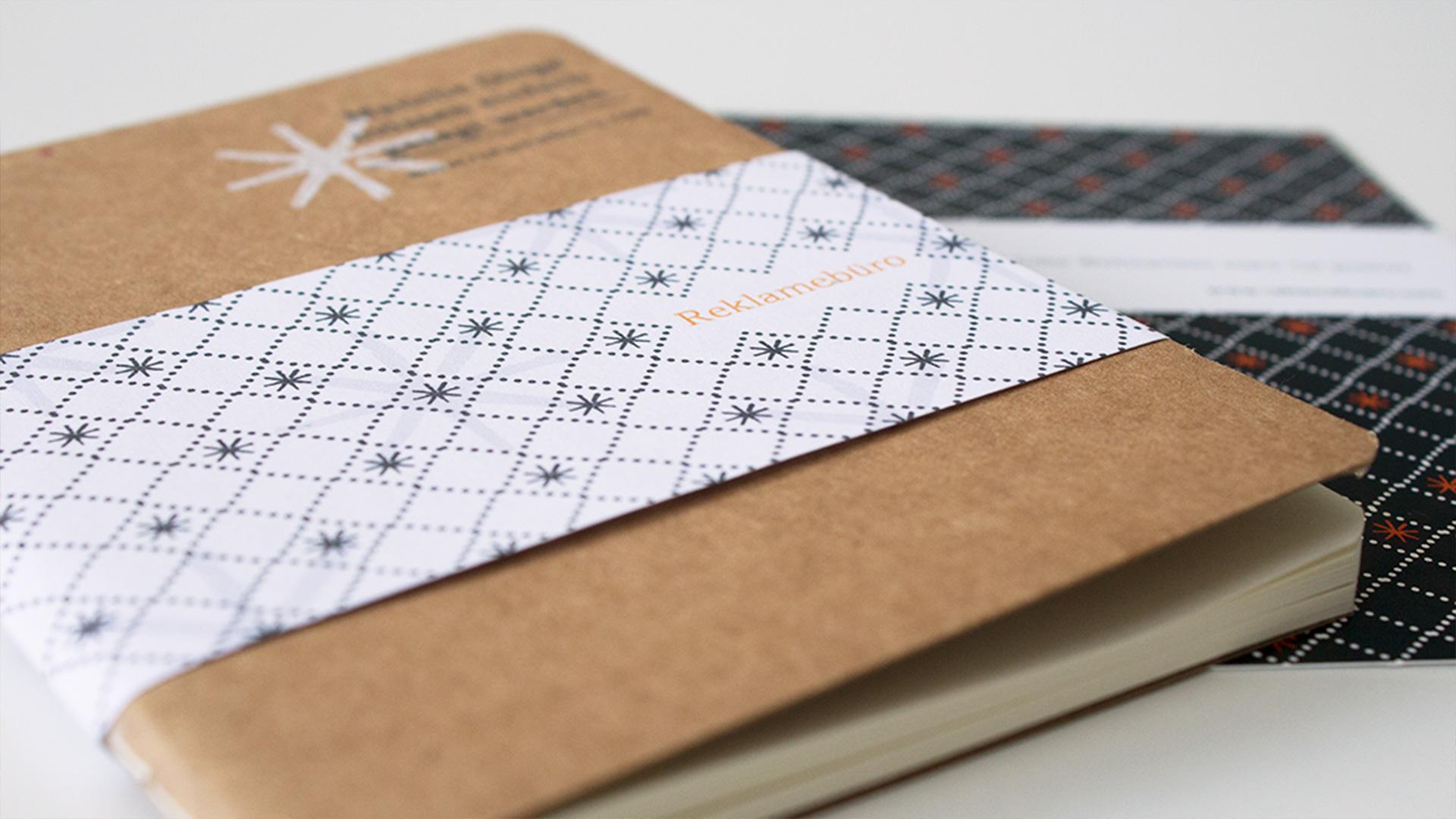 Ein Notizbuch mit einer Banderole liegt auf einer Karte mit einem durchgängigen Muster