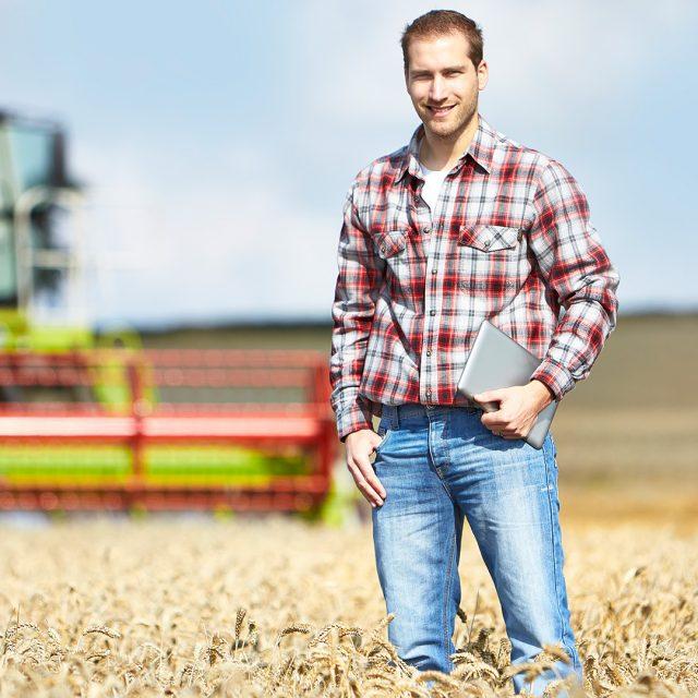 Ein Landwirt mit einm Tablet in der Hand steht auf einem Getreidefeld, dahinter ein Mähdrescher